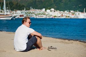 Junger Mann mit Bootschuhen am Strand